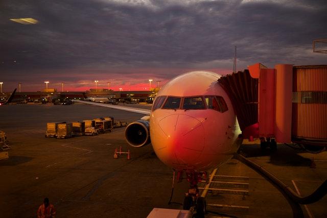 Lietadlo na letisku pripravené na nástup cestujúcich po západe slnka.jpg