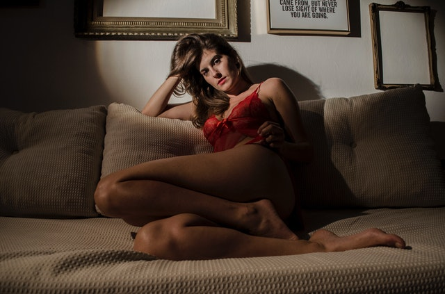 Žena v červenom erotickej spodnej bielizni sedí na gauči