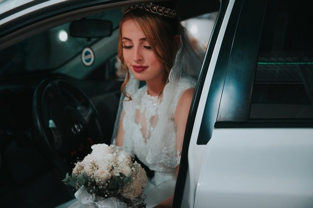 Nevesta v šatách s kyticou v rukách sedí v aute