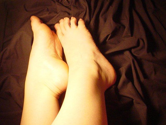 Ženské chodidlá na hnedej prikrývke