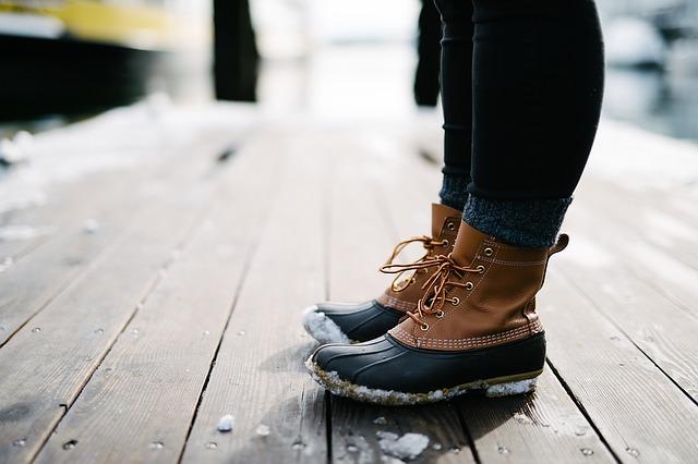 Žena v zasnežených zimných topánkach stojí na drevenej podlahe