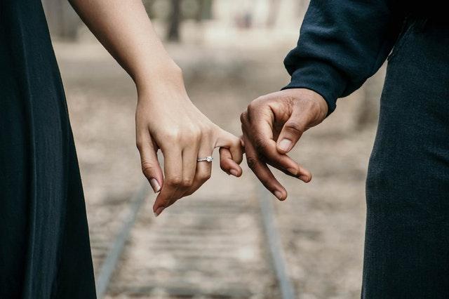 Žena s jemným prsteňom na prste drží muža za ruku.jpg
