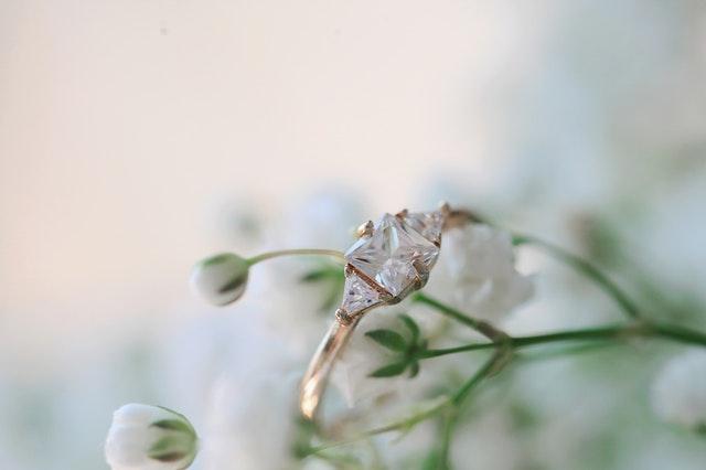 Prsteň s kameňom zavesený na bielom kvete.jpg