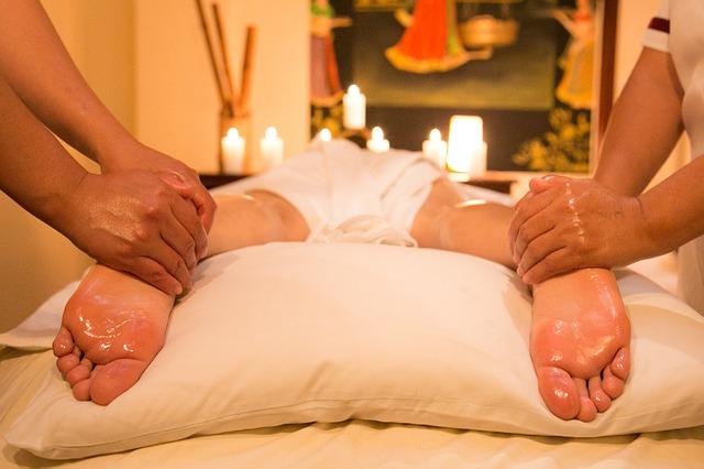 Dve osoby masírujú nohy človeka ležiaceho na ležadle v salóne.jpg