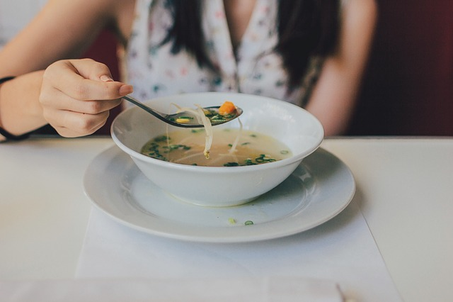 Žena si lyžicou naberá polievku z misky.jpg
